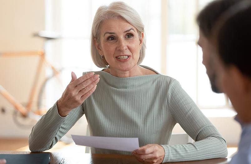 Confident mature businesswoman mentor job applicant speak at negotiations interview