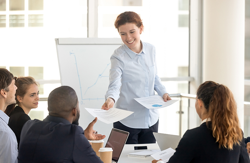 Female manager giving paper report to diverse employees at meeting